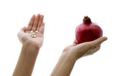 Hands holding pills and a pomegranate to illustrate exercise pill