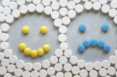 Pills forming a smiling and frowning face to illustrate antidepressants antidepressant drugs