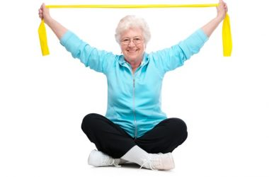 Senior woman exercising with resistance band to fight chemotherapy side effects