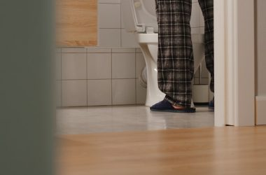 Feet of adult man with prostate problems standing in front of toilet at home