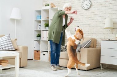 Senior woman relieving chronic pain by playing with dog