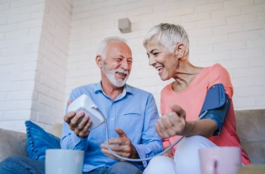 Smiling seniors checking for high blood pressure at home