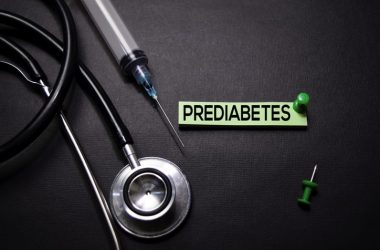 Prediabetes text on a sticky note with a stethoscope and insulin needle