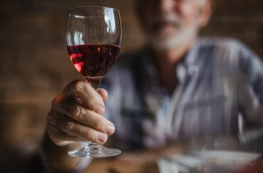 Senior man holding glass of red wine with probiotic supporting polyphenols