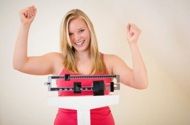 Happy woman on scale losing weight without weight-loss surgery