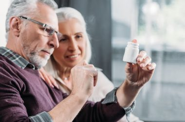 Senior couple looks at label on losartan blood pressure pill bottle