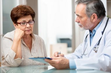 Male doctor giving senior female patient a dementia test