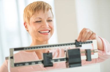 woman on scale happy about her weight loss without weight-loss surgery