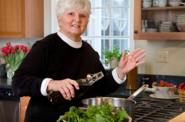 Mature woman dressed a salad with olive oil to fight dementia