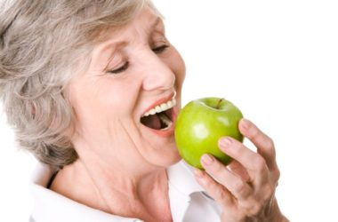 Senior woman bites into an apple boosting her cholesterol control and heart heart.