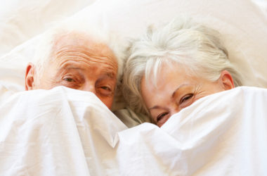 Romantic senior couple smiles under covers after blood flow and erection issues were fixed