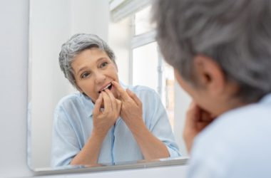 Senior woman cleaning teeth with floss to avoid gum disease and stroke