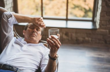 Mature man lies on sofa holding a glass of alcohol
