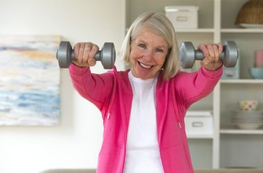 Senior lady using dumbbells exercising at home to cheat death