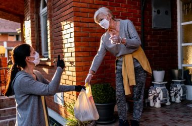 Senior woman in mask gets a food grocery delivery at home