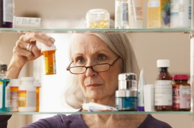 Senior woman looking at IBD prescription bottles