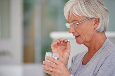 Senior woman taking vitamins and vitamin D to help support her immune system