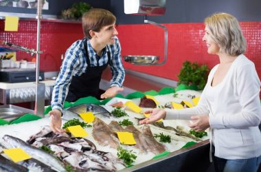 Smiling female customer buying fish to avoid cognitive decline