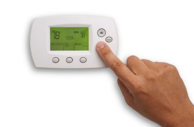 Close up of thermostat being adjusted to turn on air conditioning