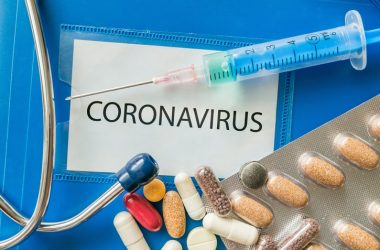 Coronavirus written on a folder with various pills and a syringe to represent potential treatments like quercetin