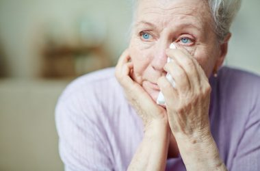 Senior woman holding tissue to eye raises risk of Alzheimer's with negative thinking