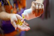 Close up of older woman pouring fish oil capsules with omega-3s into her hand