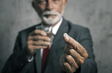 Senior man in suit holding glass of water and an aspirin
