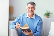 Senior man takes MagnaVive Reading Book Smiling Sitting On Couch