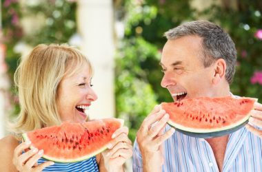 Smiling senior couple eats slices of diabetes defeating watermelon