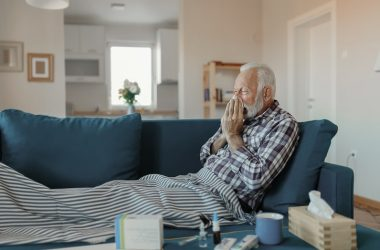senior man with common cold on sofa blowing his nose