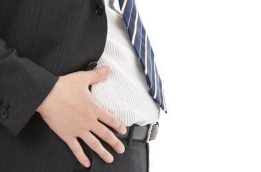 Man in suit has hand on belly fat linked to prostate cancer
