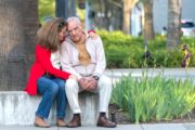 Senior man suffering from Alzheimer's sits with caregiver daughter