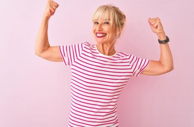 Smiling senior woman showing arm muscles fighting frailty with magnesium and vitamin D