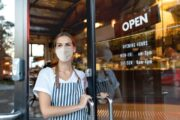 Woman stands in restaurant doorway in a mask to illustrate dining out