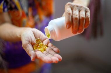 Close up of older woman pouring fish oil capsules to fight arthritis pain into her hand