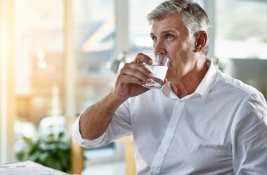 Mature man drinking a glass of atrazine laced testosterone reducing water