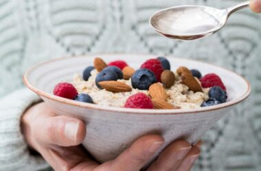 Close up of woman eating blood pressure friendly oatmeal topped with nuts and berries