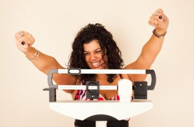 Happy woman on scale lost weight reducing coronavirus risks