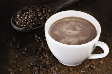 Mug of hot cocoa and a wooden spoon overflowing with chocolate cocoa nibs