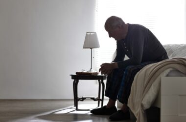 Senior man sitting on bed feeling apathy an early warning sign of dementia