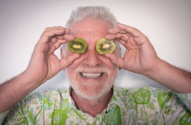 Smiling senior man holding constipation fighting kiwi slices in front of his eyes