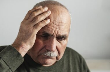 Confused senior man holding a hand to his head may have coronavirus delirium