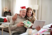 Senior couple at home at Christmas having video call with family reducing stress and heart risk