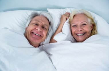 Senior couple smiling in bed after getting over bedroom blues with pine extract