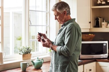 Senior man in kitchen with teapot looking at CBD oil label