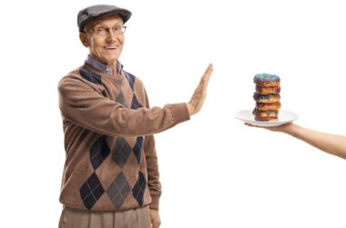 Senior man refusing a plate of simple carbohydrate packed donuts
