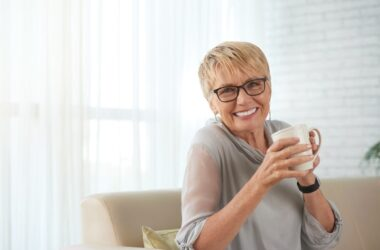 Smiling older woman drinking a cup of liver protecting coffee