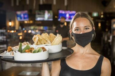 Waitress in a mask carrying a food tray because restaurants are open despite the coronavirus