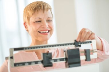 Woman on manual scale smiling happy about weight loss with CurcuTrim