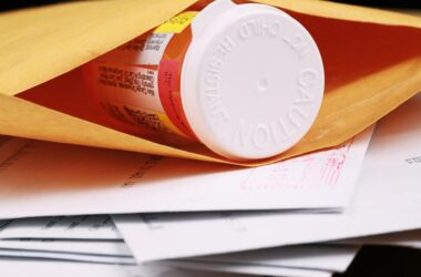 A close-up of a pill bottle in an envelope to represent mail-order medications